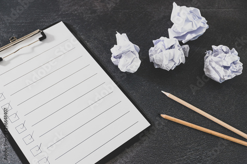 overcoming lack of productivity concept, to do list on clipboard and pencil next to scrunched papers
