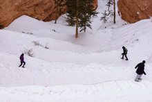 Three Hikers Hiking Down A Sno...