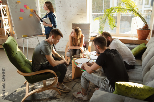 Fototapety, obrazy: Group of young caucasian office workers meeting to discuss new ideas. Creative meeting. Teamwork and brainstorming. Men and women meet in office to plan their future working. Business concept.