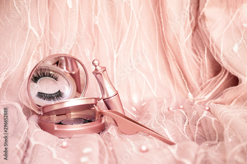 Magnetic fake artificial eyelashes in pink mirror kit, eye liner, tweezers isolated on pink background Poster Mural XXL