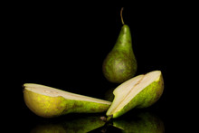 Group Of One Whole Two Halves Of Fresh Green Pear Isolated On Black Glass