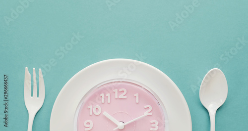 Fotografiet  Pink clock on white plate, Intermittent fasting concept, ketogenic diet, weight