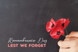 canvas print picture - Hand holding red poppy flowers, remembrance day,  Veterans day, lest we forget concept
