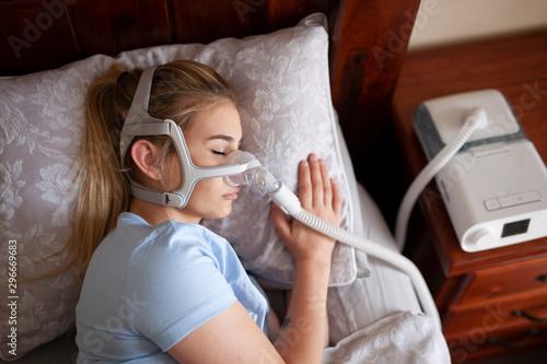Young female sleeping with cpap machine for sleep apnea Wallpaper Mural