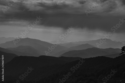 Poster Gris Beautiful shot of forested hills and mountains under a cloudy sky in black and white