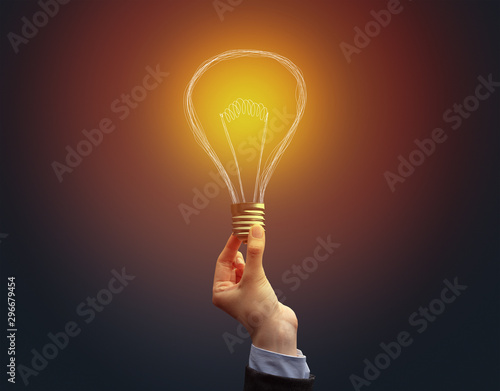 Hand holding light bulb on dark background. New idea concept