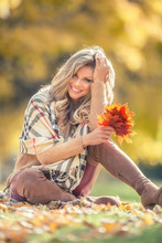 Attractive Young Woman With Sensual Smile Sitting In Autumn Park