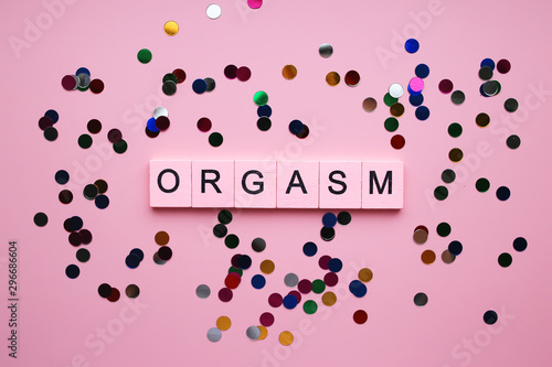 Foto Orgasm wooden words concept on pink background with colored confetti