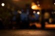canvas print picture - Empty wood table top on blur light gold bokeh of cafe restaurant in dark background