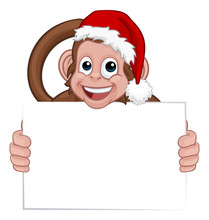 A Christmas Monkey Animal Cartoon Character In A Santa Hat Holding A Sign