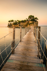 Fototapeta Mosty Beautiful sunrise at the famous Cameo island. A beautiful small island with wooden bridge and turquoise water. Zakynthos Greece. In summer.