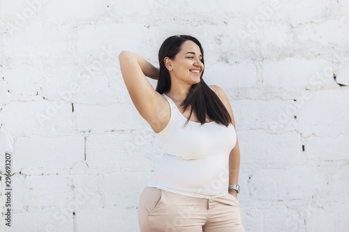 Fotografia Plus size model dressed in white shirt posing over brick wall
