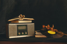 Heart-shaped Books Placed On Retro Radio Receivers With Dried Flowers And Old CD.