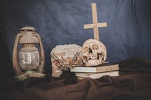 Still Life With The Skulls In Books, Old Lamps, Dry Flowers And Guns Crossed.