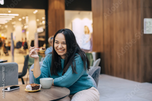 Cute plus size woman resting in cafe inside city mall - 296697837