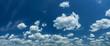 Leinwandbild Motiv Some light cumuliform clouds in the clean blue sky.