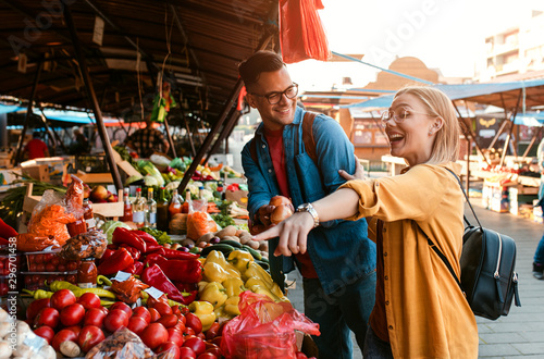 Beautiful young couple buying fresh vegetables on outdoor market. Wallpaper Mural