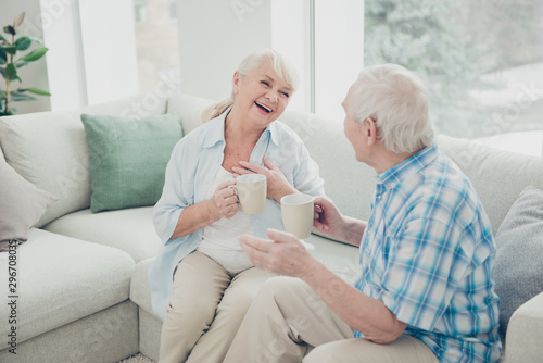Obraz Photo of two pretty aged people excited pair laughter communicating tea mugs hands comfortable flat sitting sofa indoors - fototapety do salonu