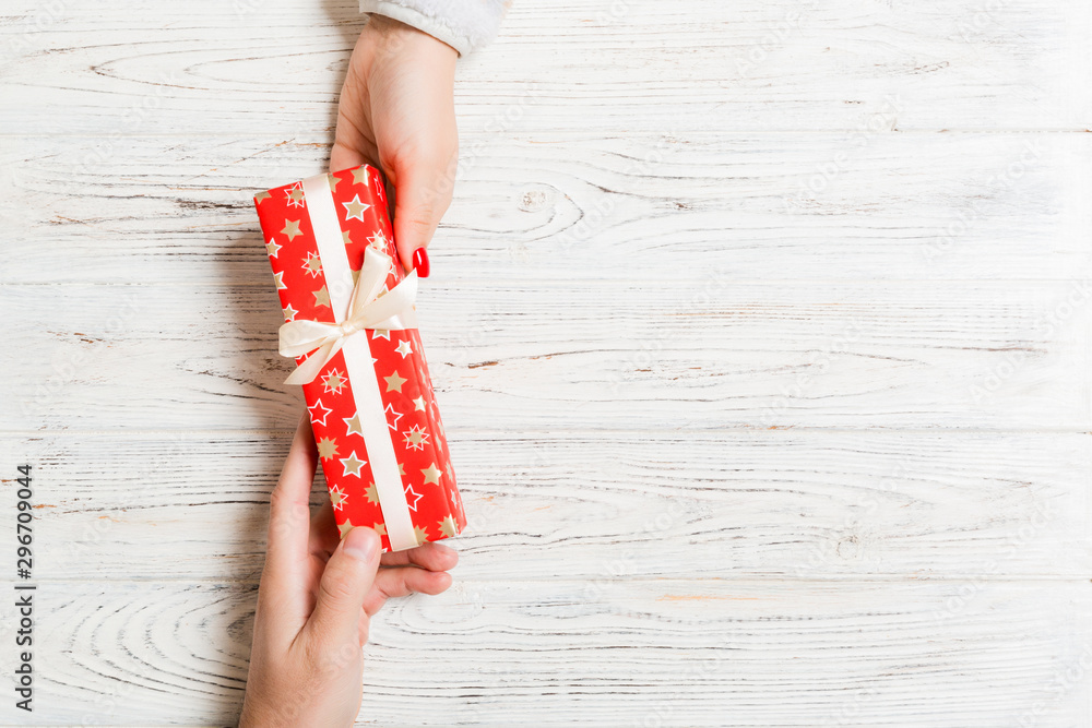 Fototapety, obrazy: Top view of giving and receiving a gift on wooden background. Present in male and female hands. Love concept. Copy space
