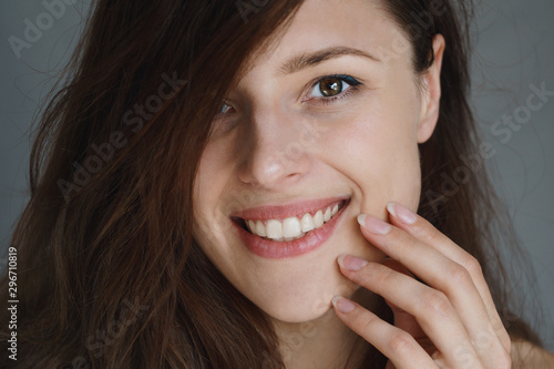 Photo Close picture of a young woman smiling and touching her glowing smooth face