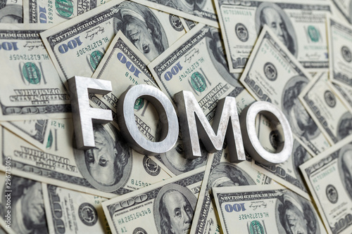 Fotografía  The word FOMO laid with aluminium letters on the US dollar banknotes background