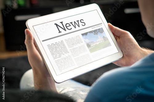 Fototapeta Man reading the news on tablet at home