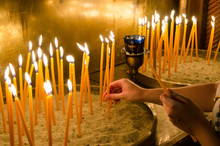 Igniting Candles In A Greek Or...