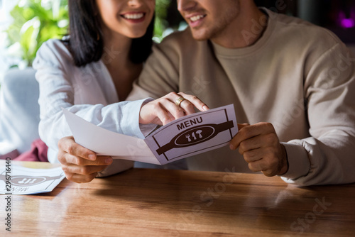 cropped view of woman pointing with finger at menu near happy man