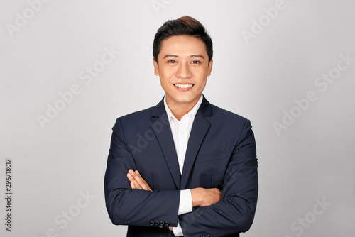 Stampa su Tela Happy Asian young businessman standing cross-armed on white background