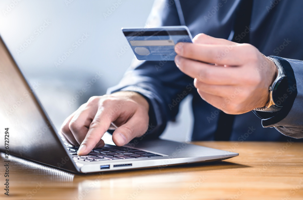 Fototapeta Safe online payment and electronic money transfer security. Pay with digital technology. Man using credit card and laptop to login to internet bank. Financial safety to prevent scam, threat and fraud.