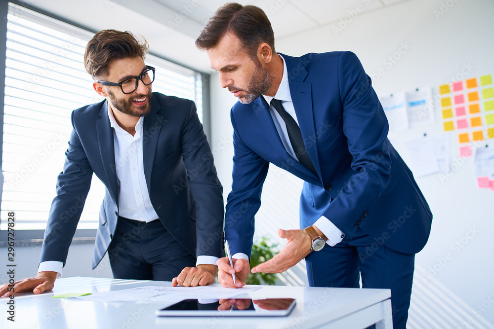 Fototapeta Two business executives looking at documents and discussing in office