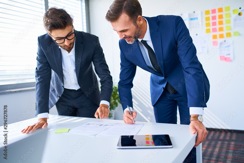 Fototapeta Two businesspeople talking over business documents in office and signing contract