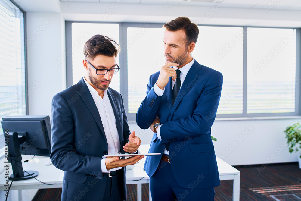 Fototapeta Two businessmen looking at tablet and discussing financial matters in the office