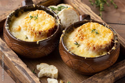 Obraz Traditional French onion soup, with croutons, Gruyere cheese, thyme. Tasty cozy, hot, autumn food - fototapety do salonu