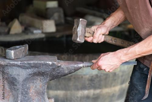 Fotografie, Tablou  un forgeron tape une enclume avec un marteau