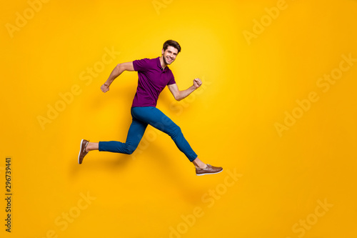 Full lenghtb body size side profile photo of hurrying urgent white casual guy running jumping in blue pants trousers purple t-shirt footwear isolated over vivid color background