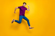 Full length body size turned photo of surprised man running as fast as he can towards shopping mall to come for sales on time wearing blue pants trousers shoes isolated vivid color background