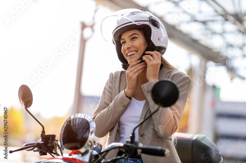 Woman on scooter tightens helmet