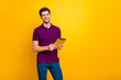 Portrait of his he nice attractive cheerful cheery content guy using digital ebook app browsing web wi-fi isolated over bright vivid shine vibrant yellow color background