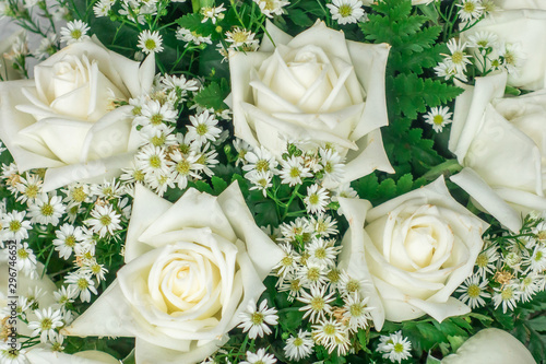 Fotografía  The closed up of rose bouquet with white small gypsophila and green leaves in the flower shop