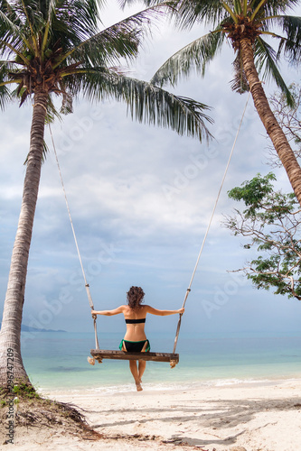 Photo  Young woman swinging on a big beach swing in Thailand