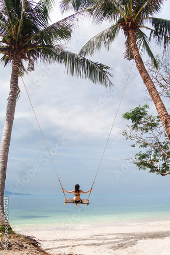 Young woman swinging on a big beach swing in Thailand Wallpaper Mural