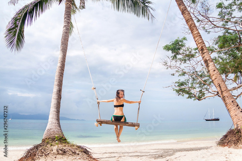 Young woman swinging on a big beach swing in Thailand Canvas Print