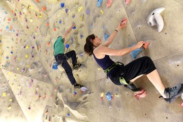 Fototapetayoung sporty couple of climbers in a climbing hall