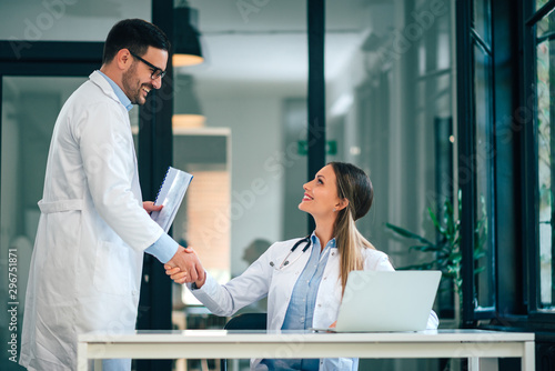 Pinturas sobre lienzo  Two confident doctors standing shake their hands in medical office