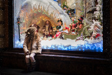 Little Girl Stands On The Streets At The Window On Christmas Eve