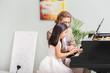 Man teaching little girl to play piano