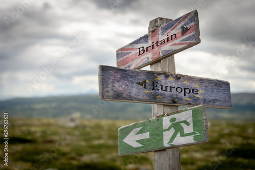 Fotografía  Britain, europe and exit text with flag on wooden signpost outdoors in nature, emergency sign to symbolize Brexit