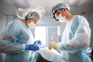 The surgeon, the dentist and the nurse, perform an operation on the patient. The concept of maintaining health and beauty.