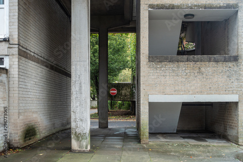 A passageway between brick walls with concrete columns supporting structure above.